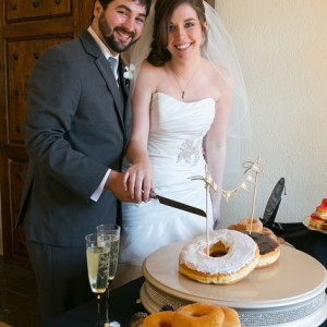 a couple standing near a party table with donuts